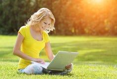 Meisje met laptop Blonde mooie jonge vrouw met notitieboekje stock foto