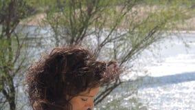 Meisje met laptop die in de verse lucht werken Een vrouw typt op laptop door de rivier stock footage