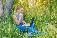 Meisje met laptop die op de telefoon in aard spreken royalty-vrije stock foto's