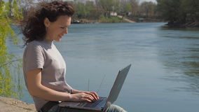 Meisje met laptop door de rivier Een jonge vrouw werkt in aard Meisje met krullend haar op de waterkant met laptop stock videobeelden