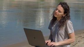 Meisje met laptop door het water Het werk aangaande de computer in de verse lucht door de rivier De lente zonnige dag in aard stock footage
