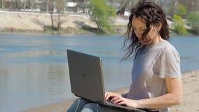 Meisje met laptop door het water Het werk aangaande de computer in de verse lucht door de rivier De lente zonnige dag in aard stock video