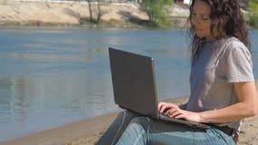 Meisje met laptop door het water Het werk aangaande de computer in de verse lucht door de rivier De lente zonnige dag in aard stock videobeelden