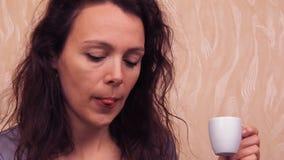 Meisje met laptop en koffie Een vrouw in een grijze kleding binnen achter laptop drinkt koffie Jonge vrouw op bank bij een koffie stock videobeelden