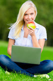 Meisje met laptop en rode appelzitting op het gras royalty-vrije stock fotografie