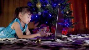 Meisje met laptop onder de Kerstboom In het Nieuwjaar is het kind onder een boom met laptop Een klein meisje onder de boom w stock footage