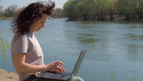 Meisje met laptop op aard Een vrouw werkt aan laptop door de rivier Een de lente zonnige dag op de waterkant stock video