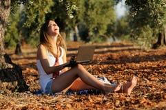 Meisje met laptop op een gebied in de herfst Royalty-vrije Stock Afbeelding