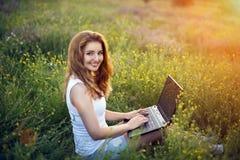 Meisje met laptop op gebied royalty-vrije stock afbeeldingen