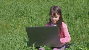 Meisje met laptop op groen gras Meisje in de aard Een mooi kind met laptop is bezig geweest met een park stock videobeelden
