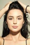Meisje met make-up op het leuke lange donkerbruine haar van de gezichtsaanraking Stock Afbeeldingen