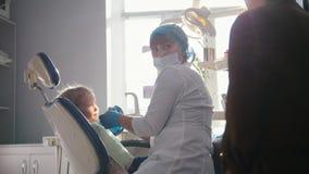 Meisje met mama als tandartsvoorzitter - het kind speelt stock videobeelden
