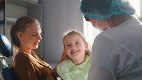Meisje met mama als tandartsvoorzitter - het kind speelt stock footage