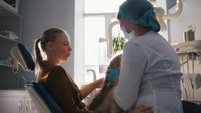 Meisje met mama als tandartsvoorzitter - het kind speelt stock video
