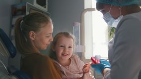 Meisje met mama in tandartsruimte - de arts onderzoekt de meisjes` s tanden stock videobeelden