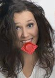 Meisje met met rood condoompak Stock Fotografie