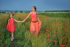 Meisje met moeder die op het papavergebied lopen Royalty-vrije Stock Afbeeldingen