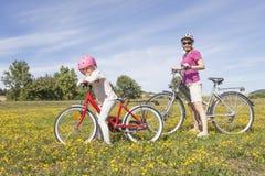 Meisje met moeder op fietsen stock afbeelding