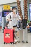 Meisje met mond GLB en koffer bij het Stationzuiden van Peking, China Stock Fotografie