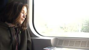 Meisje met oortelefoons die bij de trein dichtbij het venster slapen stock video