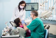 Meisje met op het eerste tandbezoek Hogere pediatrische tandarts met verpleegster die geduldige tanden behandelen op het tandkant royalty-vrije stock afbeeldingen