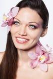 Meisje met orchideebloemen in haar Stock Foto's