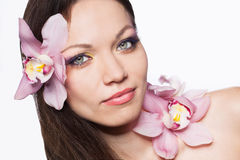 Meisje met orchideebloemen in haar Stock Afbeeldingen