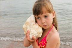Meisje met overzeese shell bij het strand Stock Afbeeldingen