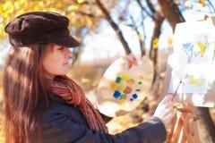 Meisje met palet in hand schetsen op papier Stock Afbeeldingen