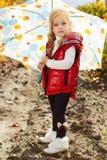 Meisje met paraplu in rood vest openlucht stock foto's