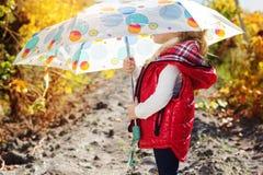 Meisje met paraplu in rood vest openlucht royalty-vrije stock foto