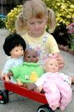 Meisje met poppen en wagen Stock Foto