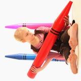 Meisje met reuzekleurpotloden Stock Fotografie