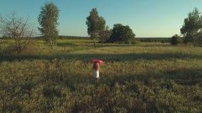 Meisje met rode paraplugangen bij het gebied stock footage