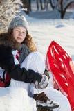 Meisje met rode plastic slee in een sneeuwpark stock afbeelding