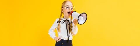 Meisje met rode vlechten op een gele achtergrond Een charmant meisje in ronde transparante glazen gilt in de luidspreker stock afbeelding