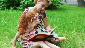 Meisje met rood haar en haar moeder gelezen boek op gazon stock video