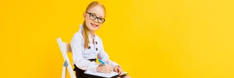Meisje met rood haar op een gele achtergrond Een charmant meisje in transparante glazen zit op een witte stoel en maakt nota's royalty-vrije stock fotografie