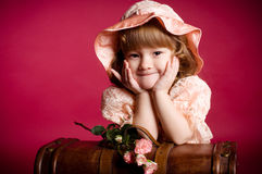Meisje met roze bloem op houten boomstam Stock Fotografie