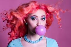 Meisje met roze haar kauwgom op een roze achtergrond en stock fotografie