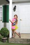 Meisje met roze handtastribunes op witte portiek stock foto