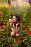 Meisje met rozen in de tuin Stock Foto's