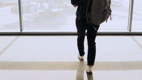 Meisje met rugzakgangen aan het venster van de luchthavenzitkamer De vrouwelijke passagier met smartphone wacht in terminal Onder stock footage