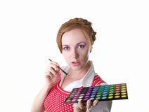 Meisje met schoonheidsmiddelenborstels stock foto's