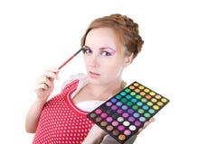 Meisje met schoonheidsmiddelenborstels stock foto