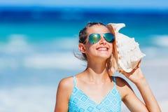 Meisje met shell bij het strand stock afbeelding