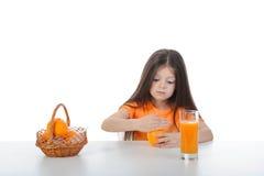Meisje met sinaasappel in hun handen bij de lijst Stock Foto