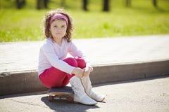 Meisje met skateboard voor de gang Stock Foto
