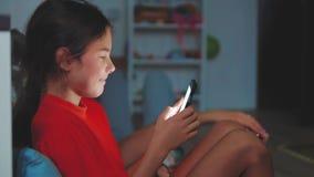 Meisje met smartphone die in een bed, bedtijd liggen online spelen van meisje de speelsmartphone op Internet thuis stock videobeelden