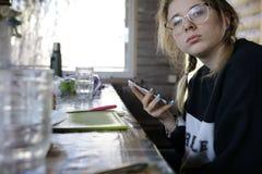Meisje met smartphone in keuken royalty-vrije stock afbeeldingen